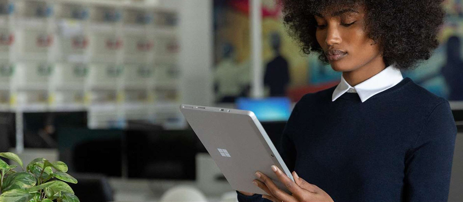 A woman works with the Surface Go 2 in tablet mode