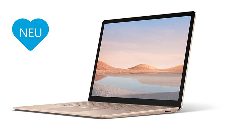 Der Surface Laptop 4 in Sandstein ist aufgeklappt aus einer seitlichen Perspektive zu sehen mit blauem Herz links neben dem Surface auf dem NEU steht