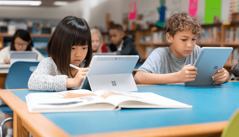 Zwei Kinder sitzen in einem Klassenraum und arbeiten an zwei Surface Go