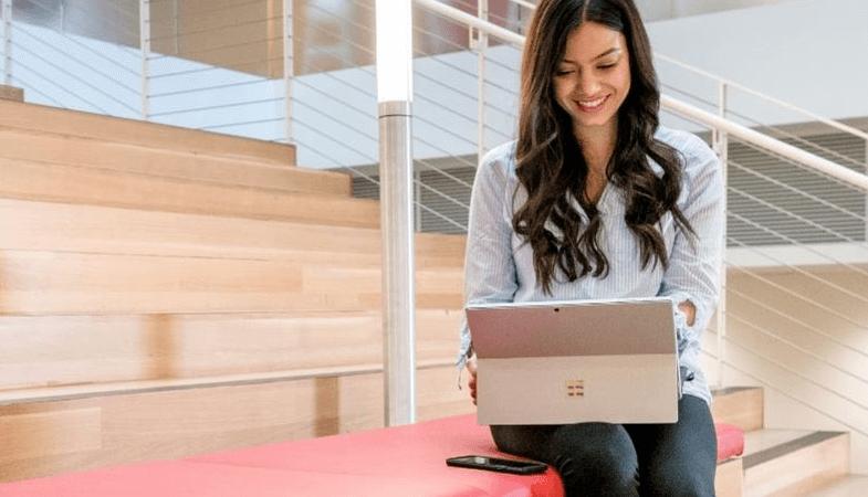 Eine ältere Schülerin sitzt auf den Treppen eines Schulgebäudes und arbeitet am Surface Pro