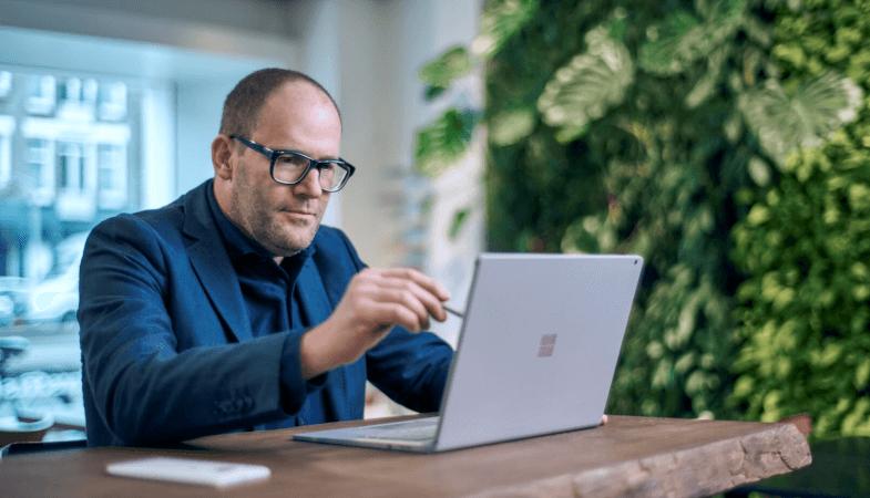 Ein Mann arbeitet an einem Tisch auf dem Display des Surface Books mit dem Surface Pen