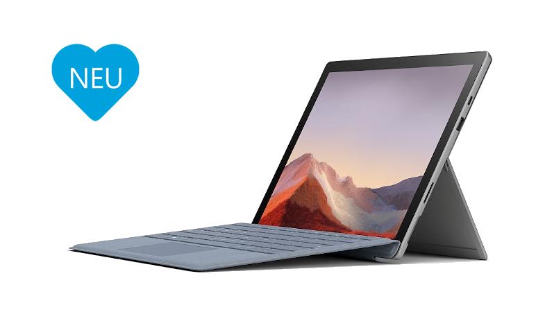 Surface Pro 7 Plus im Laptop-Modus mit dem Surface Pro Signature Type Cover in Eisblau mit blauem Herz links neben dem Surface auf dem NEU steht