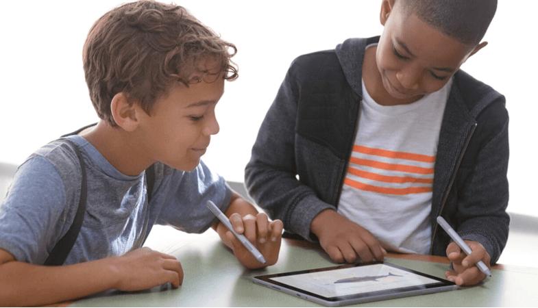 Zwei Kinder erledigen mit zwei Surface Pens Aufgaben auf dem Surface Go im Tablet-Modus