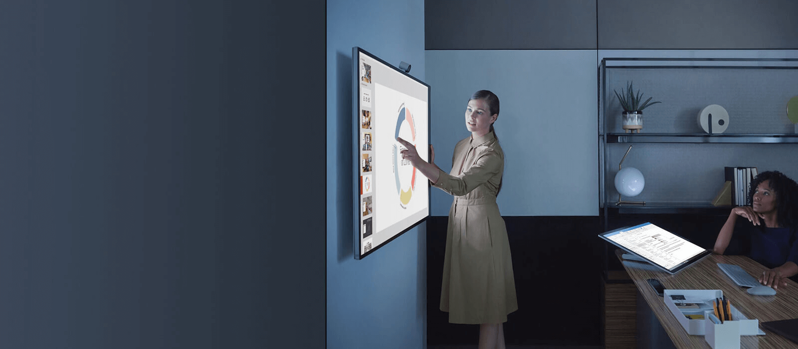One women is presenting something to another women on the Surface Hub 2