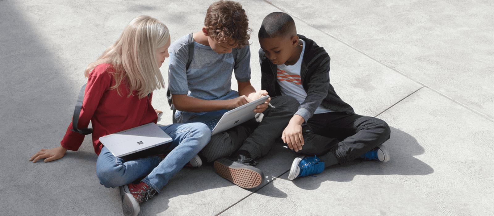 Drei Kinder sitzen auf dem Schulhof und schauen gemeinsam auf den Bildschirm eines Surface Go