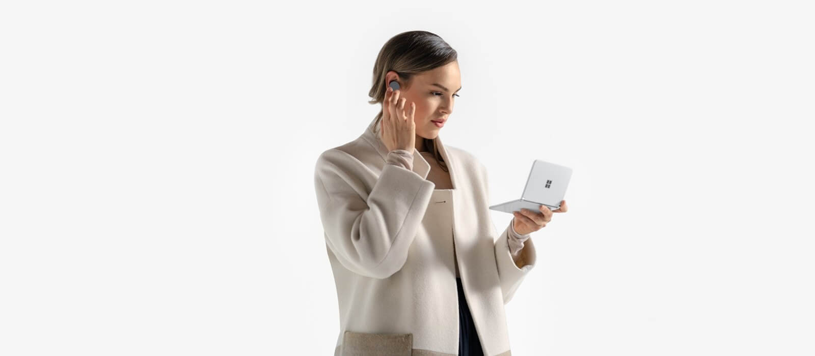 A woman holds the Surface Duo unfolded in one hand, with the other hand she taps on a Surface Earbud she is wearing in her ear