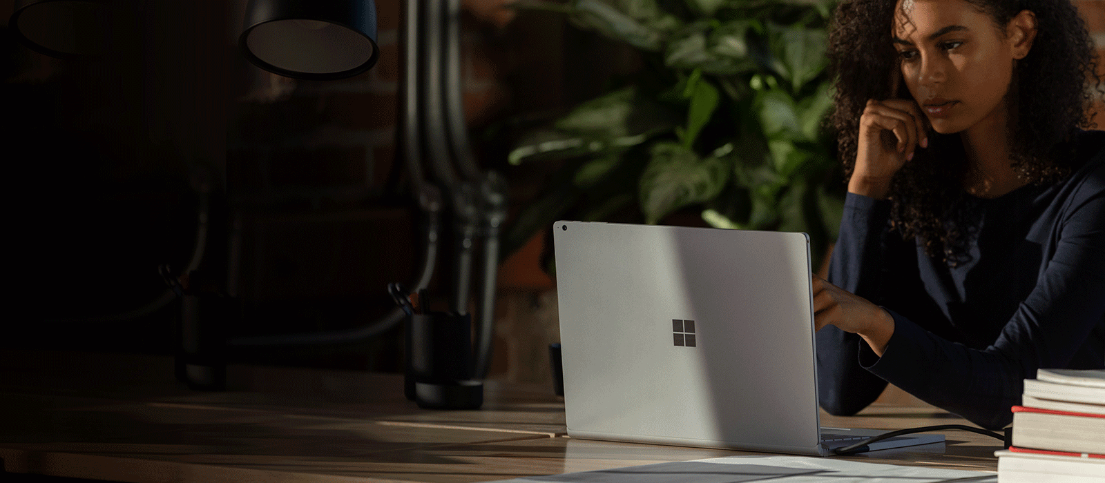 A woman is working at her desk with the Surface Book 3 in laptop mode and uses the touch screen