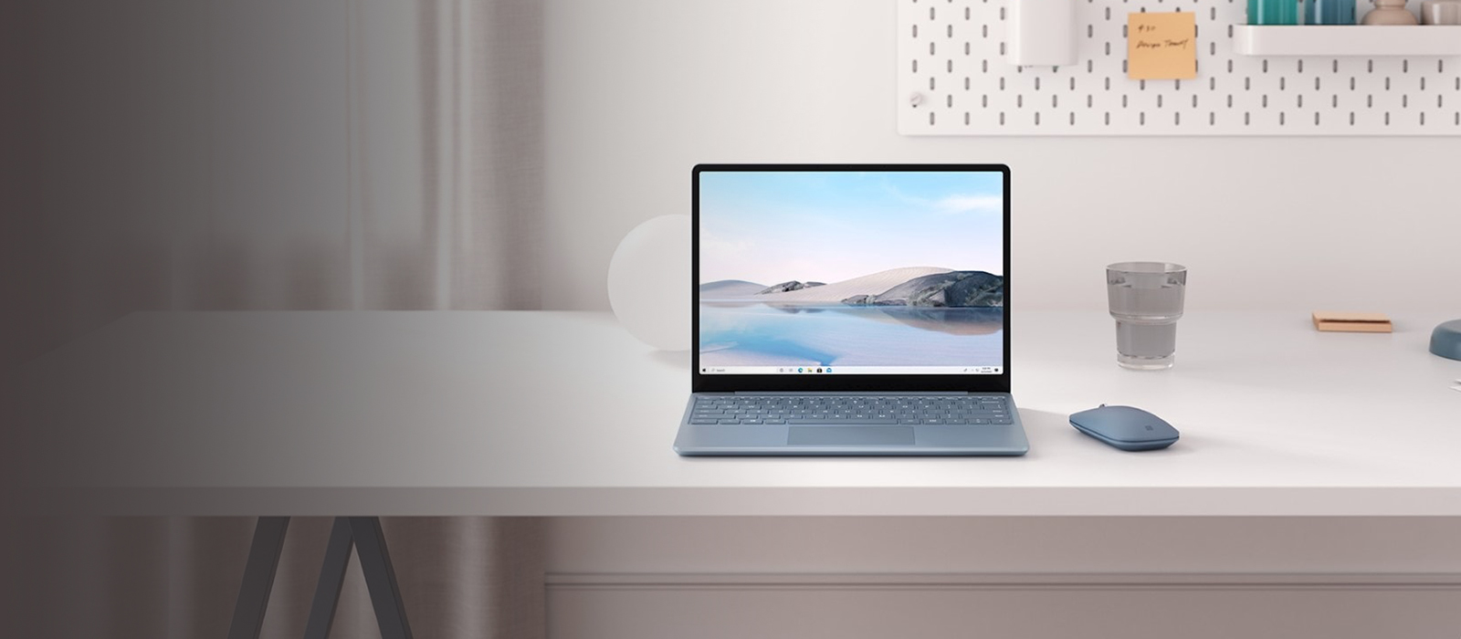 The Surface Laptop Go in ice blue is placed on a desk