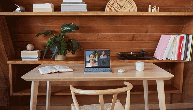 Ein eisblauer Surface Laptop Go steht auf einem Schreibtisch vor einem Regal