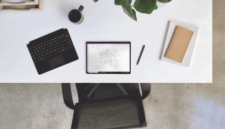 Das Surface Pro X ist neben dem Signature Keyboard in Schwarz sowie dem Slim Pen in einer Schreibtisch-Szenerie platziert