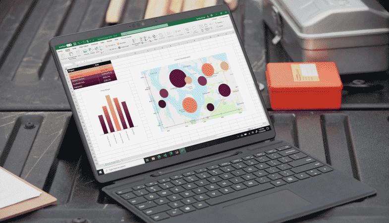 Das Surface Pro X steht im Tablet-Modus mit einem geöffneten Excel-Sheet auf dem Display auf einem schwarzen Untergrund, im Hintergrund ist Werkzeugmaterial erkennbar