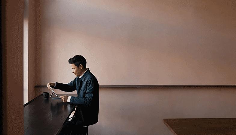 Ein Mann bringt das Surface Go 2 vom Laptop- in den Tablet-Modus
