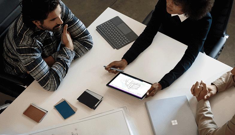 Ein Team arbeitet an einem Tisch zusammen und nutzt das Surface Go 2